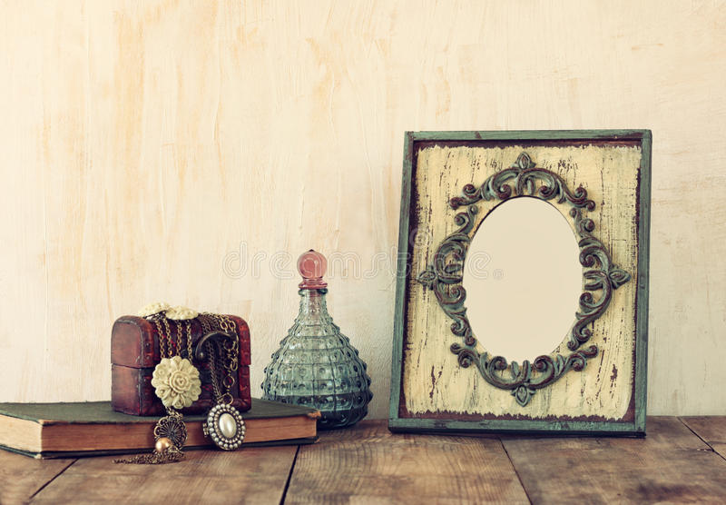 Image of victorian vintage antique classical frame, jewelry and perfume bottles on wooden table. filtered image royalty free stock photography
