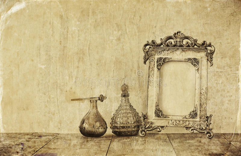 Image of victorian vintage antique classical frame and perfume bottles on wooden table. filtered image stock illustration