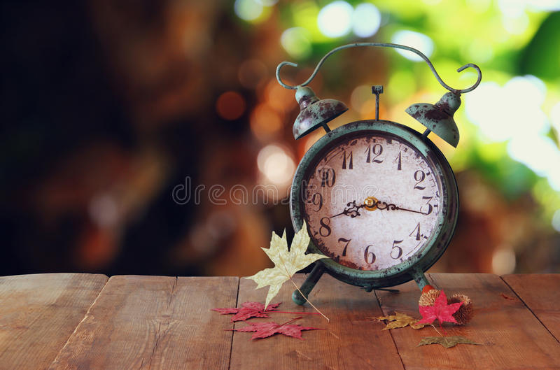 Image of vintage alarm clock next to autumn leaves on wooden table in front of abstract blurred background. retro filtered stock images