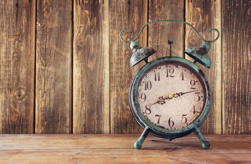 Image of vintage alarm clock on wooden table in front of wooden background. retro filtered stock image