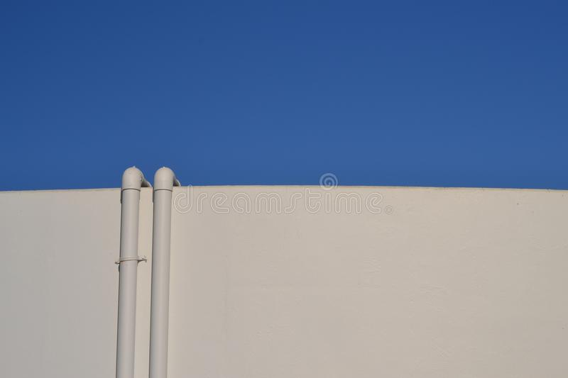 Half Minimalism. This image was composed in Florida at a wastewater treatment facility. With a half and half thought. Blue sky and white digestion tank, thank stock image