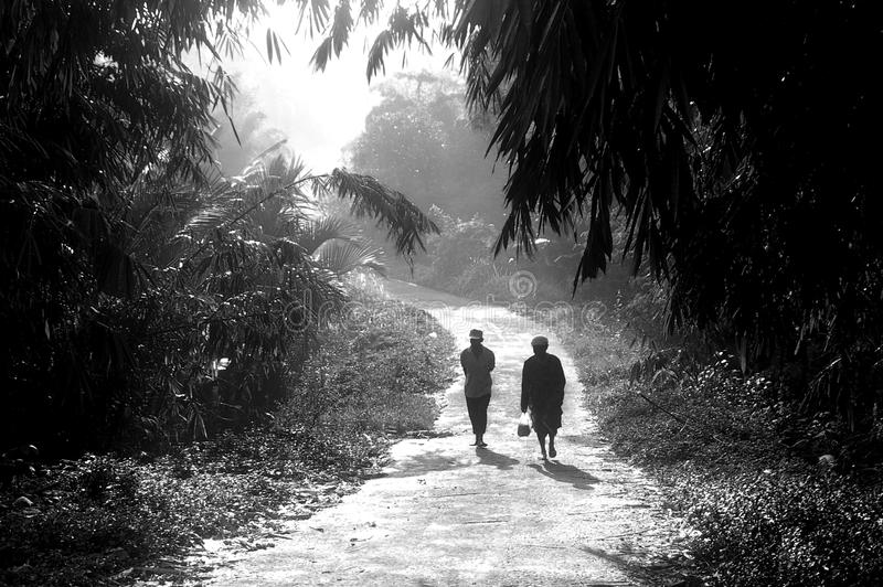 A couple is walking in the village under morning sunshine royalty free stock image