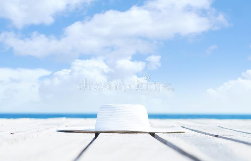 Image of a white hat on a wooden pier. Vacation, holiday and tr. Image of a white hat on a wooden pier. Vacation and traveling concept stock photos