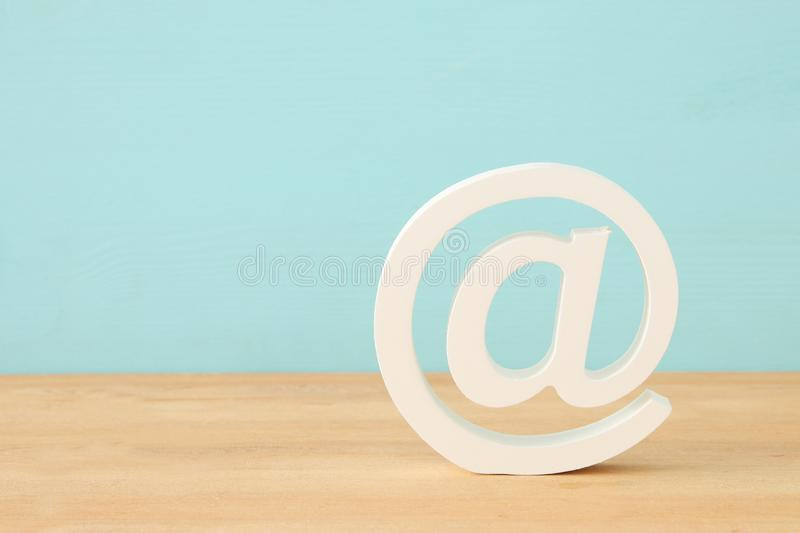 image of white mail icon over wooden desk. royalty free stock photography