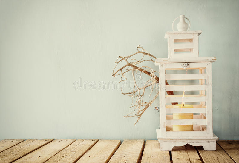 Image of white wooden vintage lantern with burning candle and tree branches on wooden table. retro filtered image stock photography