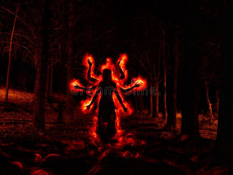 Image of woman in the dark forest silhouetted with red fire effect on the sides royalty free stock photos