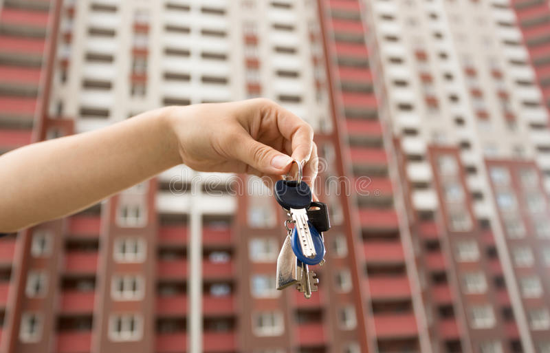 Image of woman holding keys from new apartment in front of new b stock image