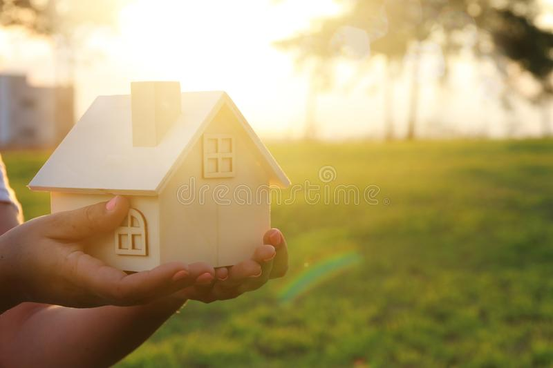 Image of woman holding small wooden house outdoors at sunset light. stock photos