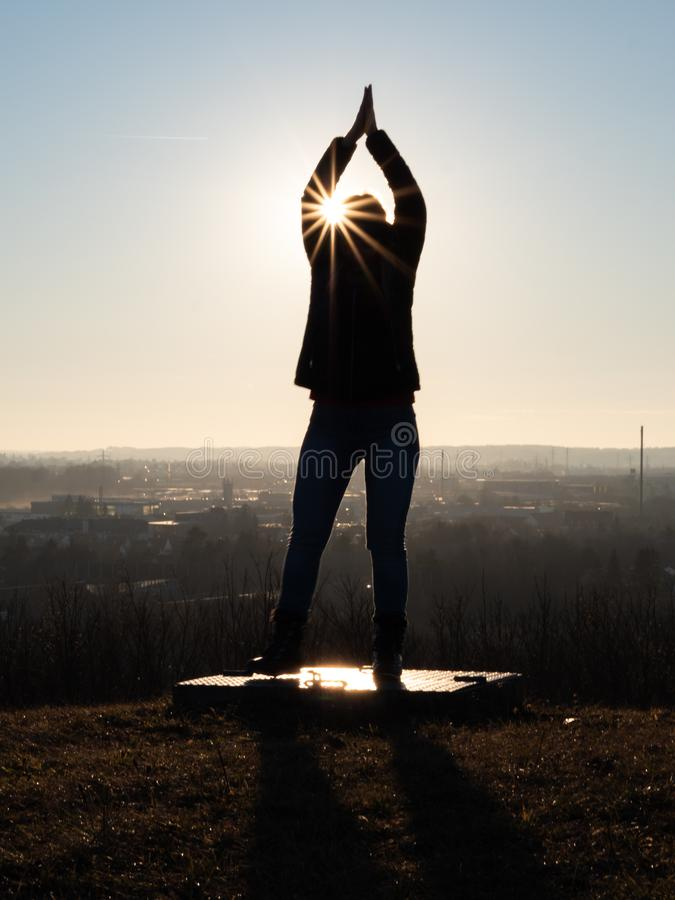 Image of woman`s silhouette performing gymnastics on a platform with sun rays. And sun star royalty free stock photo