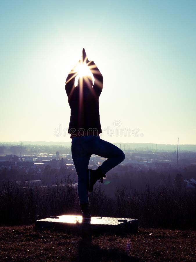 Image of woman`s silhouette performing a yoga tree on a platform with sun rays. And sun star stock photography