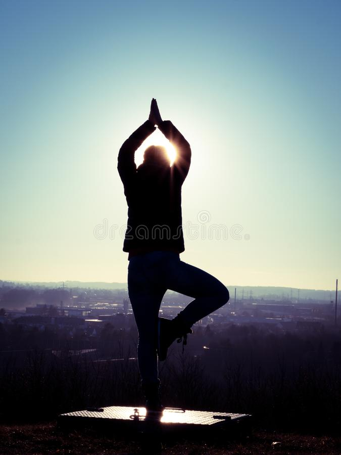 Image of woman`s silhouette performing a yoga tree on a platform with sun rays. And sun star stock image