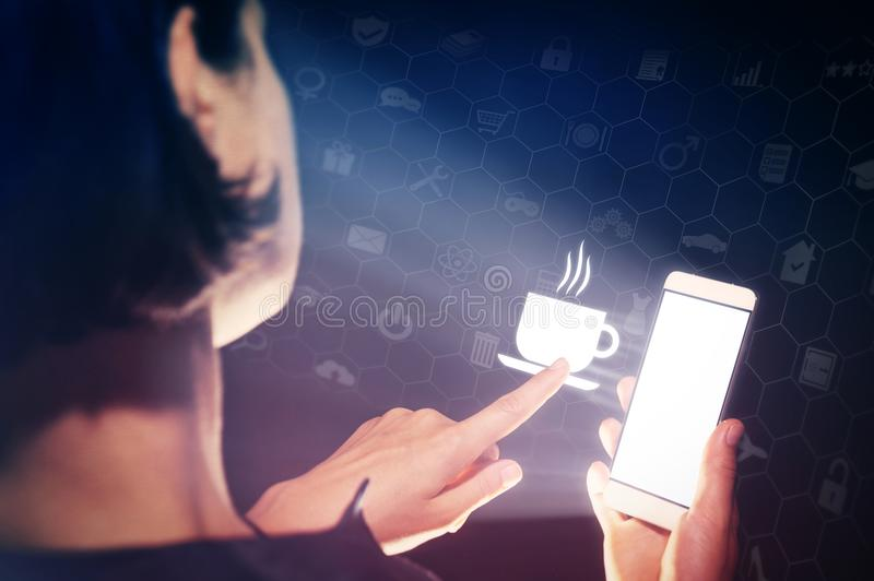 Food delivery using online services. Image of a woman with a smartphone in her hand. She touch the icon cup with hot drink. She lookin a menu, chooses hot drinks royalty free stock image