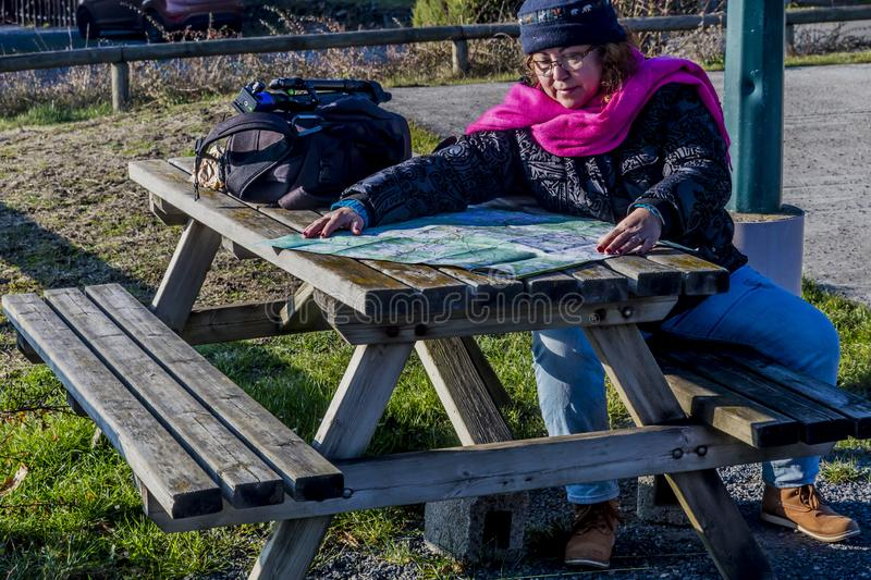 Image of a woman with warm clothes sitting looking or checks the route on a paper map stock photo