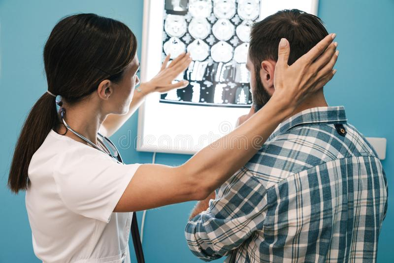 Image of woman doctor and patient man looking at x-ray scan in hospital royalty free stock photos