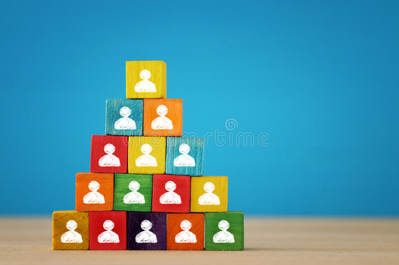 Image of a wood blocks pyramid with people icons over wooden table, human resources and management concept. Image of a wood blocks pyramid with people icons stock photography
