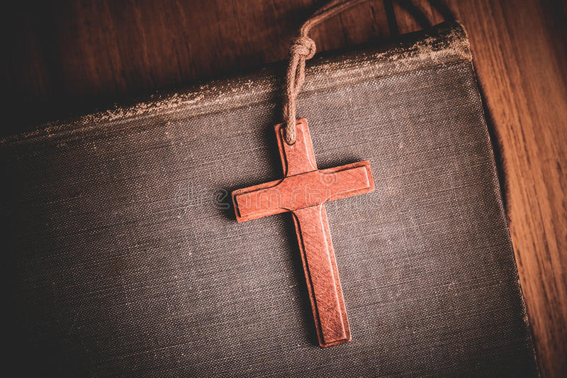 Image of wooden cross on bible background royalty free stock images