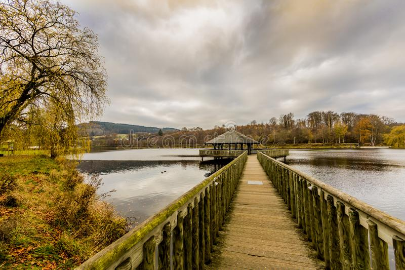 Image of a wooden footpath leading to a gazebo in the middle of the Doyards Lake in Vielsalm. Beautiful image of a wooden footpath leading to a gazebo in the royalty free stock photos