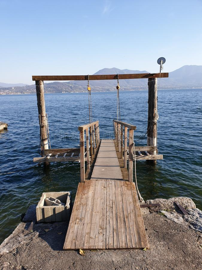 Image of wooden pier at the lake of maggiore royalty free stock photography