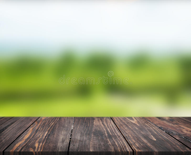 Image of wooden table in front of abstract blurred background of garden. can be used for display or montage your products. Mock up stock image