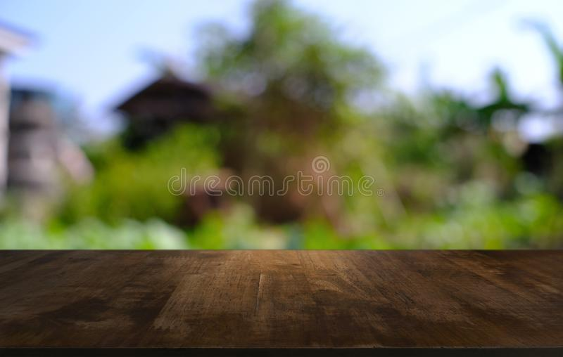 image of wooden table in front of abstract blurred background of stock photos