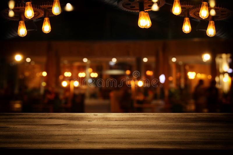 Image of wooden table in front of abstract blurred restaurant li stock image