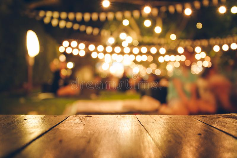 Image of wooden table in front of abstract blurred restaurant lights background stock images