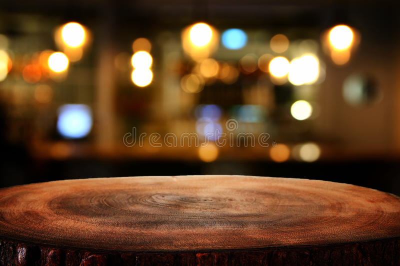 Image of wooden table in front of abstract blurred restaurant lights background royalty free stock photography