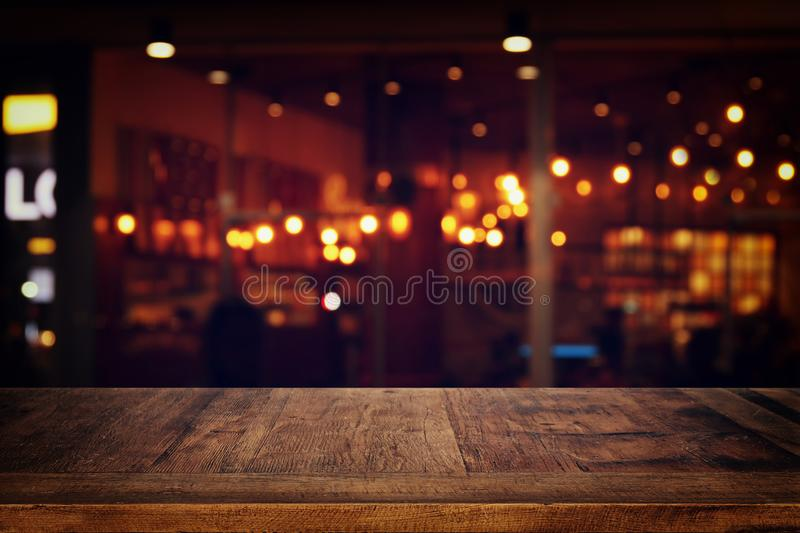 Image of wooden table in front of abstract blurred restaurant lights background. stock photography