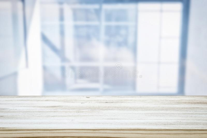 image of wooden table in front of abstract blurred window light background. stock photo
