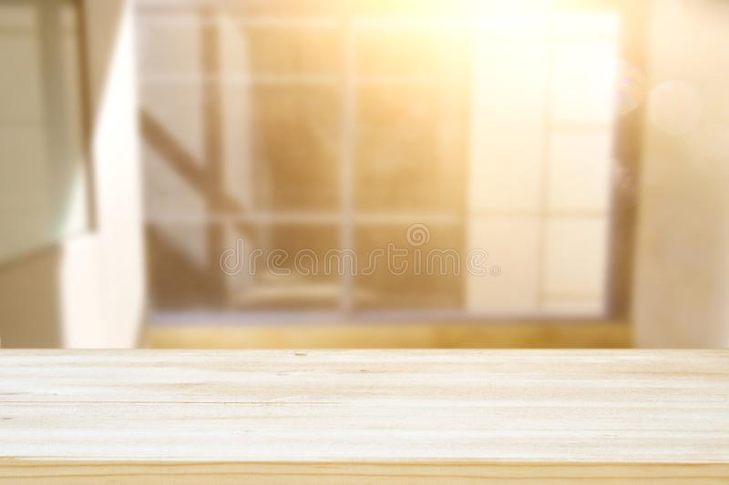 image of wooden table in front of abstract blurred window light background. royalty free stock photo