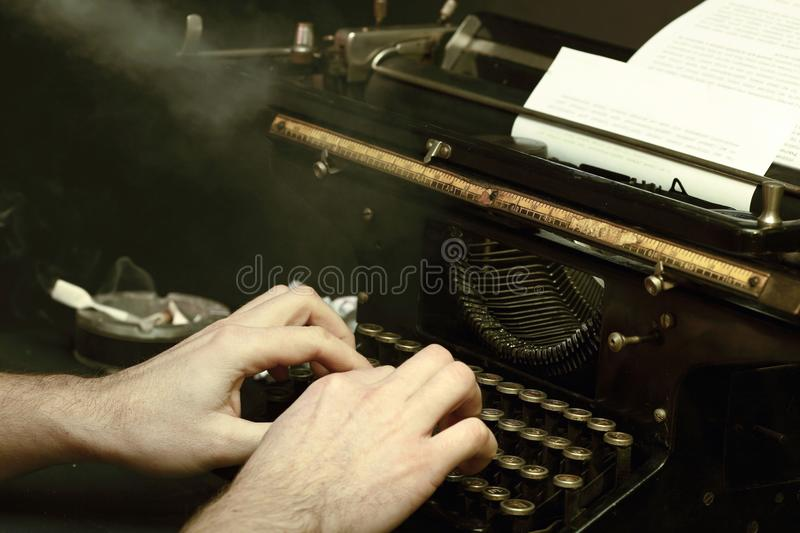 The typewriter image in retrostyle. The image of the writer or the reporter behind the typewriter in retrostyle with a cigaret smoke stock images