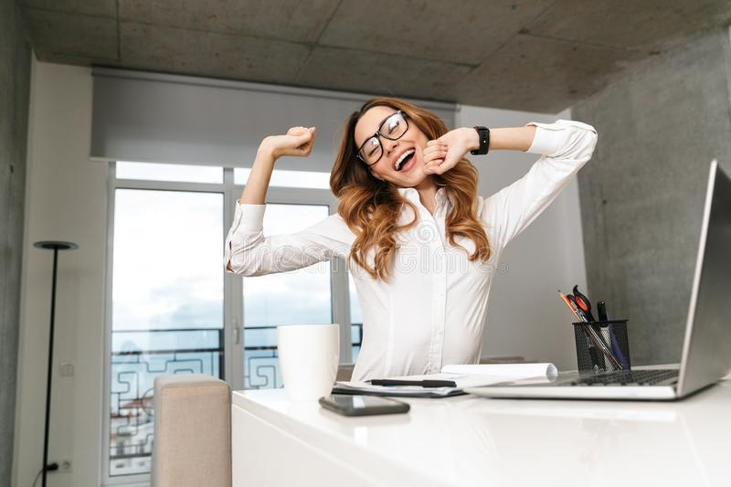 Yawning stretching young business woman dressed in formal clothes shirt indoors using laptop computer. Image of yawning stretching young business woman dressed royalty free stock photography
