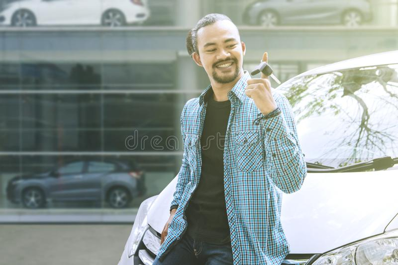 Young man twisting his new car key in the dealer royalty free stock images