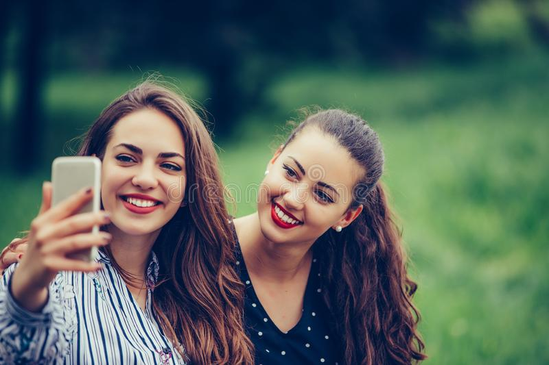 Image of young amazing women friends, students sitting in the park make selfie by mobile phone royalty free stock images