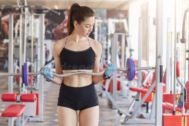 Image of young athletics girl training hard with barbell in gym. Fitness muscled woman in sport clothing, with ponytail has royalty free stock photo