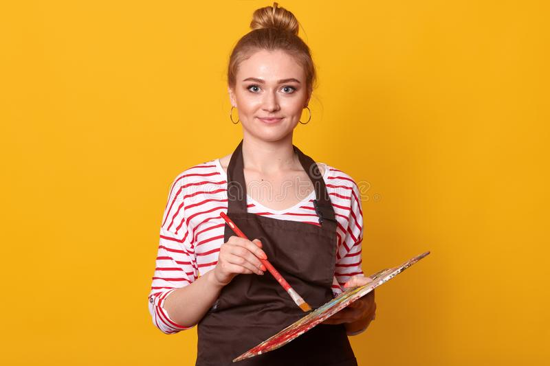 Image of young attractive pleasant wearing stripped sweatshirt, brown apron and earrings, looking directly at camera, holding royalty free stock photos