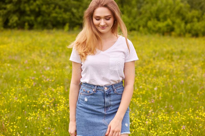 Image of young beautiful Caucasian girl in white t shirt and blue denim skirt, posing in meadow and looking down, has long stock image
