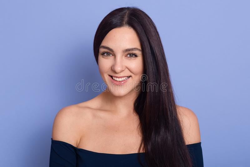 Image of young beautiful gorgeous young woman with perfect skin wearing dark blue dress posing with bare shoulders. Beauty fasion stock photography