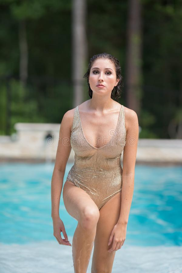 Image of a young beautiful woman walking out of the swimming pool stock photography