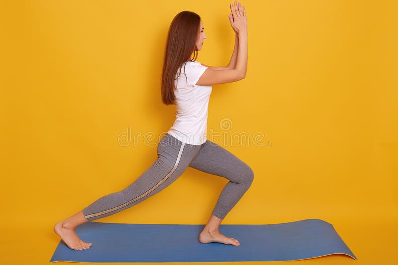 Image of young beautiful woman yoga posing isalated over yellow studio background, adorable female wearing white casual t shirt stock photos