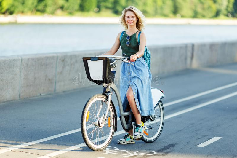 Image of young blonde in long denim skirt sitting on bike on road in city royalty free stock photography
