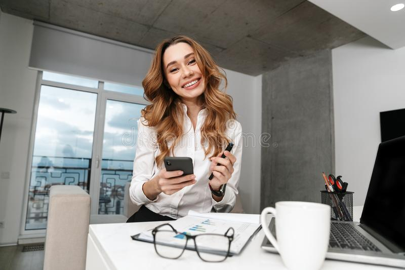 Business woman dressed in formal clothes shirt indoors using mobile phone. Image of young business woman dressed in formal clothes shirt indoors using mobile royalty free stock image