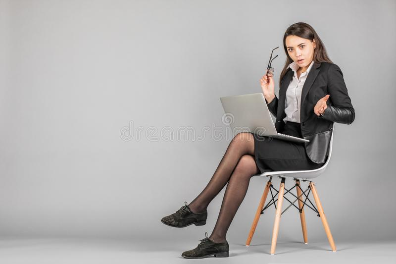Image of young business woman posing isolated over grey wall background sitting on stool using computer royalty free stock images