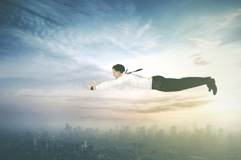 Young businessman flying above downtown. Image of young businessman looks happy while flying above downtown with fast motion stock images