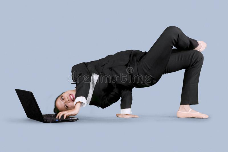 Businesswoman using a laptop with dance pose stock photo