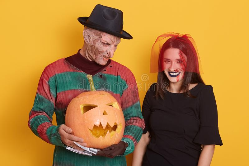 Image of young couple celebrate Halloween, male in striped sweater and black hat, has knives instead of fingers, female in black stock photo