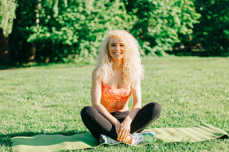 Image of young curly-haired sports woman practicing yoga on rug stock photography