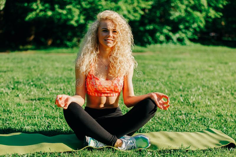 Image of young curly-haired sports woman practicing yoga on rug stock photos