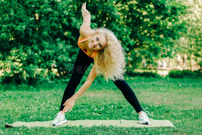 Image of young curly-haired sports woman practicing yoga on rug stock images