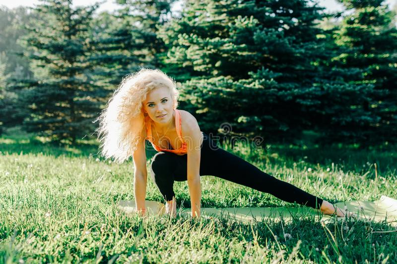 Image of young curly-haired sports woman practicing yoga on rug royalty free stock photos